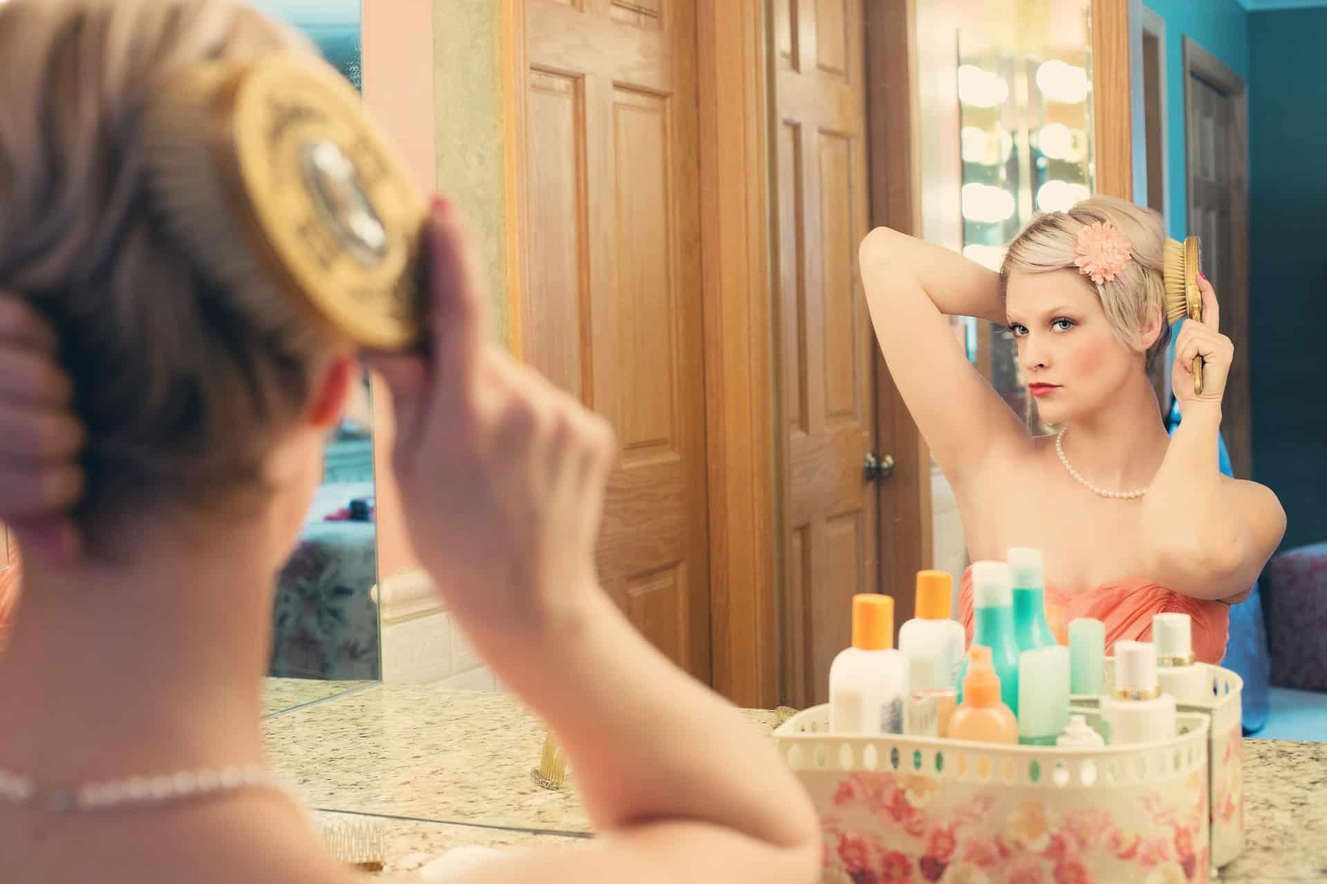 Frau schminkt sich im Spiegel